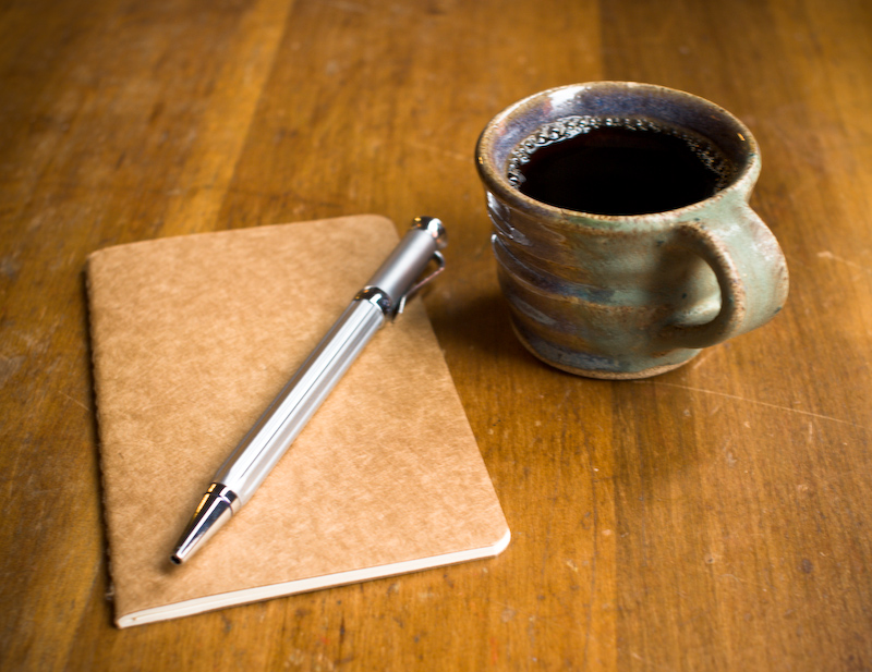Moleskine notebook, silver pen, and a mug of coffee